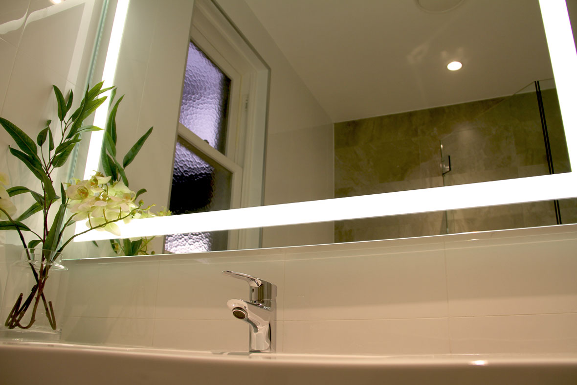 Verge Lighted Bathroom Mirror front view, showing the mirror installed in a bathroom.