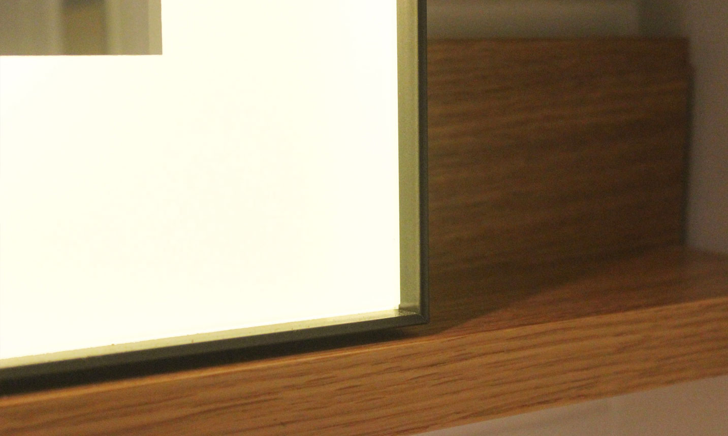 The Edge Metal Frame Lighted Mirror pictured in a 5 star hotel bathroom, corner close up.